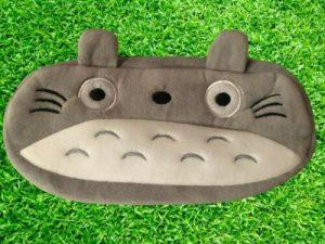 Astuccio con Totoro grigio porta penne, porta trucchi morbido. Nello sfondo si vede un prato verde.